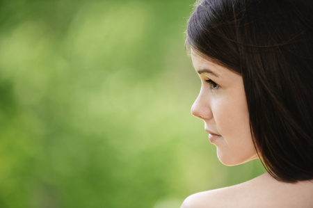 Close-up portrait of young appealing brunette woman at summer green park. Stock Photo - 9980734