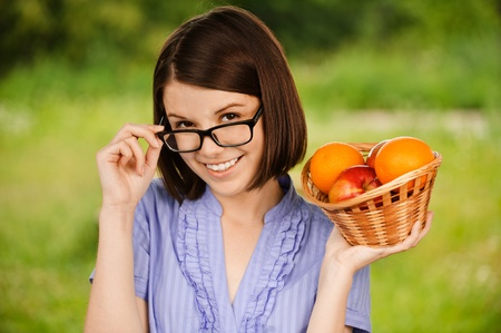 Portrait of young beautiful smiling woman wearing eyeglasses and blue blouse holding basket full of ripe juicy fruits at summer green park. photo