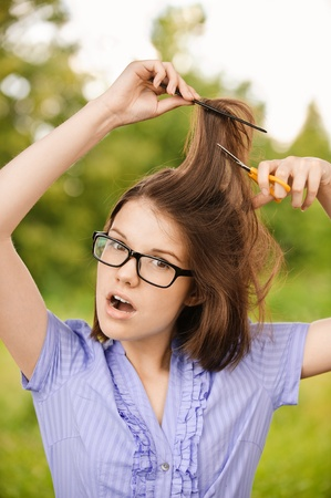 Portrait of young beautiful shocked brunette woman wearing glasses with comb and scissors cutting her hair at summer green park. photo