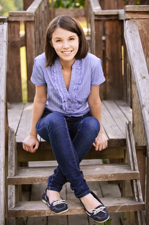 Young beautiful dark-haired smiling woman wearing blue blouse and jeans sitting on wooden staircase at summer park. Stock Photo - 9980781
