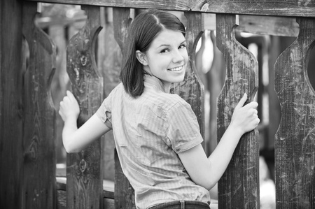 Black-and-white portrait of young beautiful smiling brunette holding wooden fence at summer park. Stock Photo - 9980755