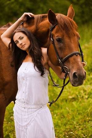 Portrait of young beautiful woman wearing white dress standing at summer green park with brown kind horse. photo