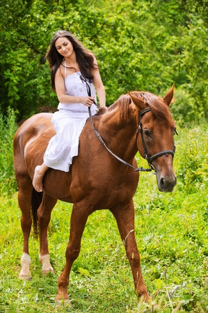 Portrait of young beautiful brunette woman wearing white dress riding dark horse at summer green forest. Stock Photo - 9980794