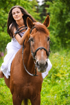 Portrait of young beautiful smiling brunette woman wearing white dress riding dark horse at summer green forest. photo