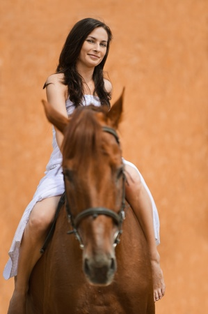 barn girls: Portrait of young content long-haired brunette woman wearing white dress riding brown horse.