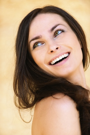 Close-up portrait of young attractive brunette smiling woman looking somewhere against yellow background. photo