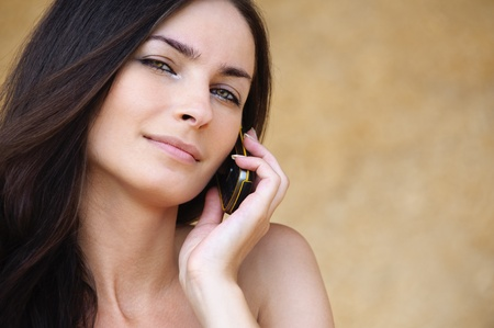 Close-up portrait of young attractive brunette woman speaking on mobile phone against yellow background. Stock Photo - 9980793