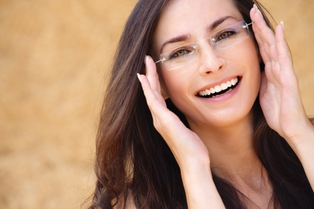 Close-up portrait of young beautiful brunette woman wearing glasses against beige background. photo