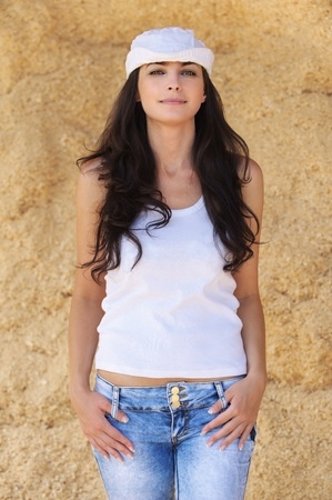 Portrait of young beautiful positive brunette woman wearing white cap, white t-shirt and jeans against yellow background. photo