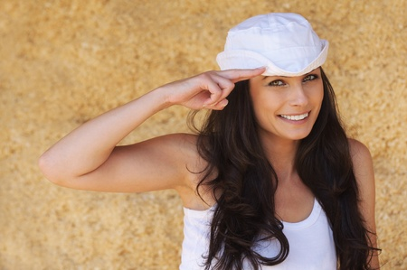 Portrait of young attractive brunette woman wearing marine cap and saluting against yellow background. Stock Photo - 9980803