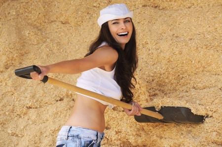 Portrait of young beautiful cheerful woman with spade against yellow background. photo