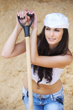 Portrait of young beautiful brunette woman wearing white cap, t-shirt and jeans holding spade and looking somewhere against yellow background. Stock Photo - 9980785