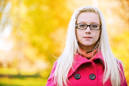 dispassionate: Portrait of young serious long-haired blond woman wearing eyeglasses and pink coat and standing at autumn park.