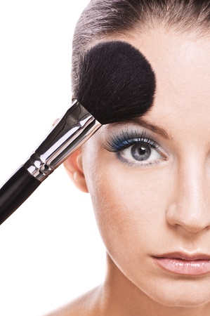 maquillage: Close-up portrait of young beautiful woman holding brush and making herself up against white background. Stock Photo