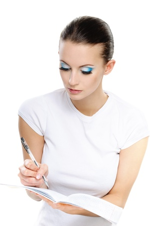 Portrait of young attractive brunette woman wearing white t-shirt and writing something against white background. Stock Photo - 9980815
