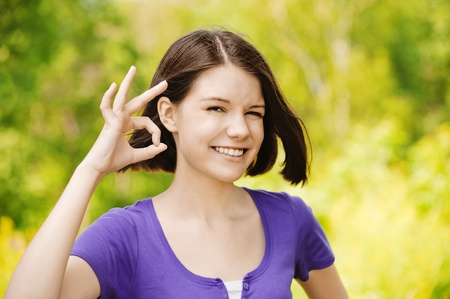 artful: Portrait of young attractive brunette woman showing ok sign at summer green park. Stock Photo