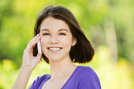 Portrait of young attractive happy brunette woman speaking on mobile phone at summer green park. Stock Photo - 9980975