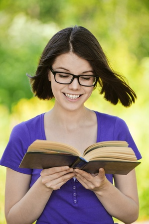 Portrait of young smiling cheerful woman wearing eyeglasses and violet blouse reading interesting book at summer green park. Stock Photo - 9980976