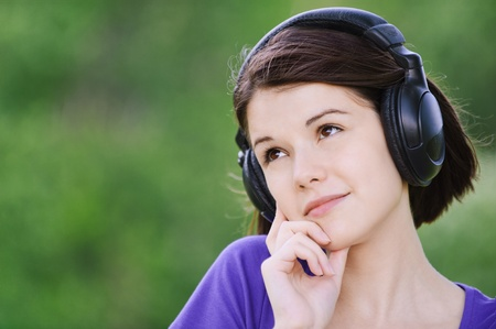 Close-up portrait of young beautiful brunette woman wearing headphones and propping up her face at summer green park. photo
