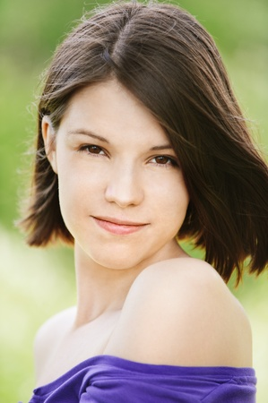 pleasant: Close-up portrait of young pleasant dark-haired woman at summer green park. Stock Photo