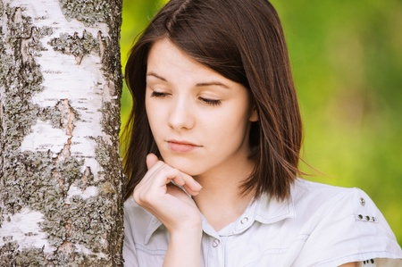 bother: Portrait of young meditative brunette woman propping up her face near birch tree at summer green park.