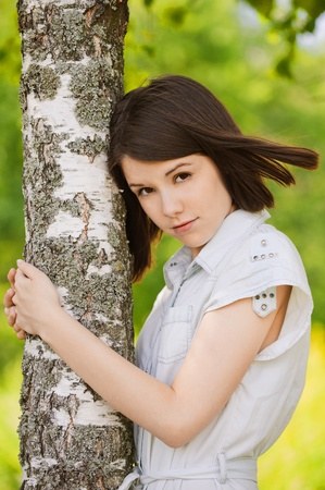 appealing attractive: Portrait of young attractive dark-haired woman wearing white chemise embracing birch tree at summer green park.