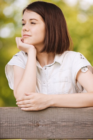 Portrait of young beautiful pensive dark-haired woman wearing white chemise at summer green park. Stock Photo - 9980968