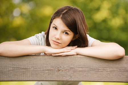 Portrait of young charming sad brunette woman with head laid on her arms at summer green park. photo