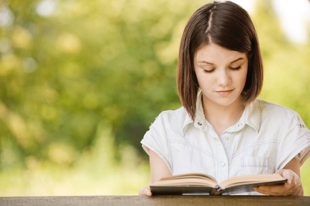Portrait of young beautiful serious cute dark-haired girl reading engaging book and wearing white chemise at summer green park. Stock Photo - 9980943