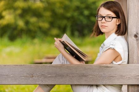 earnest: Retrato de atractiva seria Morena joven vistiendo ropa blanca, leyendo el libro, sentado en el Parque de verano verde.