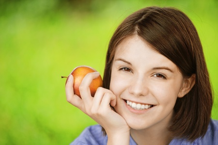 Close-up portrait of young smiling brunette woman holding red apple at summer green park. photo
