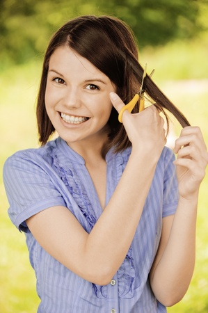 Portrait of young attractive brunette woman cutting her hair, wearing blue blouse at summer green park. Stock Photo - 9980979