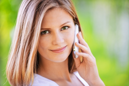 Close-up portrait of young fascinating cute fair-haired woman talking on mobile phone at summer green park.