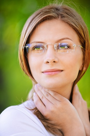Close-up portrait of young beautiful woman wearing eyeglasses looking somewhere at summer green park. Stock Photo
