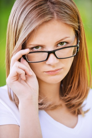 discontented: Close-up portrait of young beautiful strict blonde woman looking above her eyeglasses at summer green park.