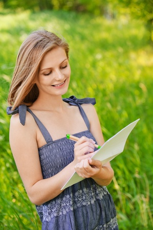 Portrait of young cheerful woman writing or painting something on sheet of paper, wearing blue jean dress, standing at summer green park. Stock Photo - 9981012