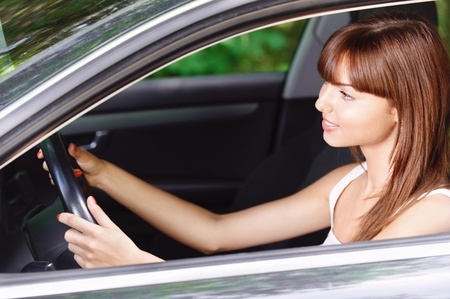 Portrait of young beautiful brunette smiling woman driving car. photo