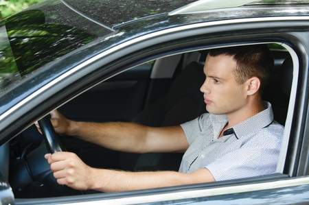 Portrait of young dark-haired handsome man driving car. Stock Photo - 10141894