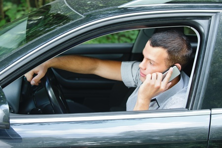 Portrait of young handsome dark-haired man driving car and speaking on mobile phone. photo