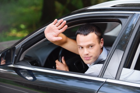 Portrait of young attractive handsome brunette man driving car and greeting somebody with hand.