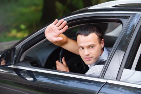 saluta: Ritratto di giovane attraente un'auto bello bruna guida l'uomo e qualcuno saluto con la mano. Archivio Fotografico