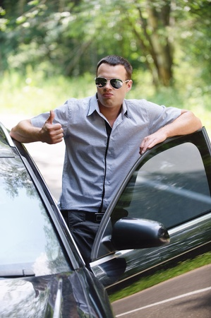 nice weather: Portrait of young handsome man wearing sunglasses and showing thumbs-up gesture, standing near car. Stock Photo