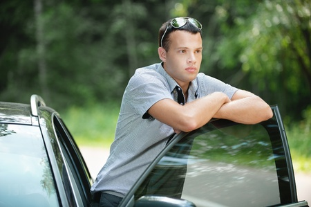 interested: Portrait of young sad pensive man wearing sunglasses standing near car. Stock Photo