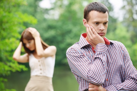 parting: Two young pensive people having quarrel or facing some problems at summer green park. Stock Photo