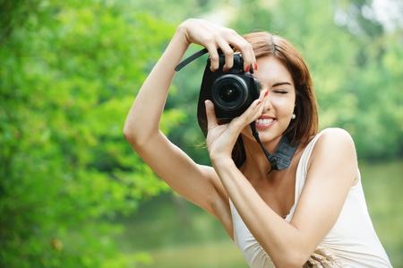 Portrait of young charmante Woman holding Fotoapparat und Einnahme Foto im grünen Sommerpark.