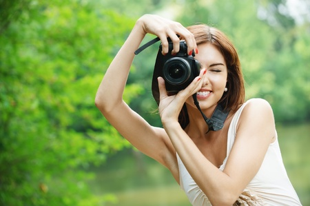 Portrait of young charming woman holding photocamera and taking photo at summer green park.