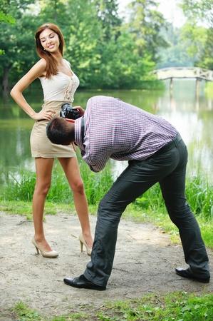 fashionable couple: Fot�grafo toma fotos de la joven y bella mujer Morena llevaba vestido beige en el Parque de verano verde.