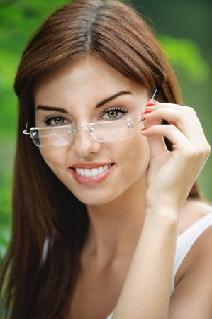 Close-up portrait of young attractive brunette woman wearing eyeglasses at summer green park. photo