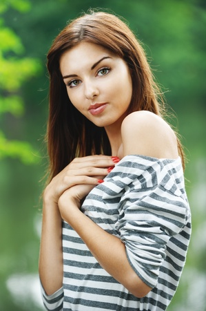 engaging: Portrait of young beautiful brunette woman wearing striped blouse at summer green park.