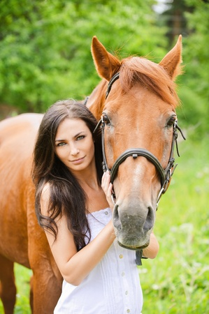 Portrait of young attractive brunette woman wearing white dress with horse at summer green park. photo